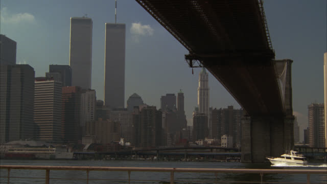 wide angle est of new york city manhattan skyline, pov from under brooklyn bridge. east river. world trade center in bg. skyscrapers and high rise office or apartment buildings. boat in water. - 1990 stock videos & royalty-free footage