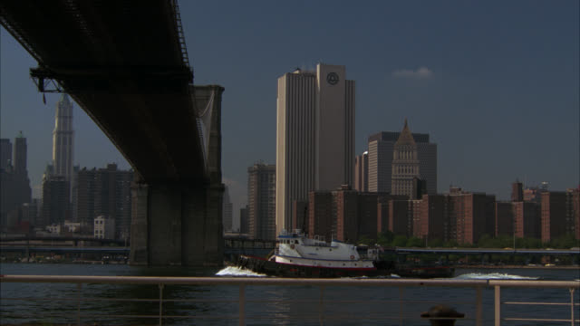 pan right to left of new york city manhattan skyline, pov from under brooklyn bridge. east river. world trade center in bg. skyscrapers and high rise office or apartment buildings. boat in water. - entertainment center stock videos and b-roll footage