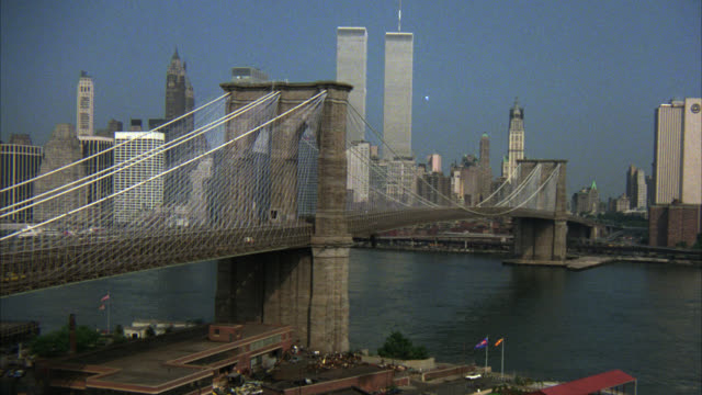zoom in on american flag under brooklyn bridge from new york city skyline. skyscrapers or high rise office buildings. world trade center or twin towers in bg. east river. manhattan. - world trade center manhattan video stock e b–roll