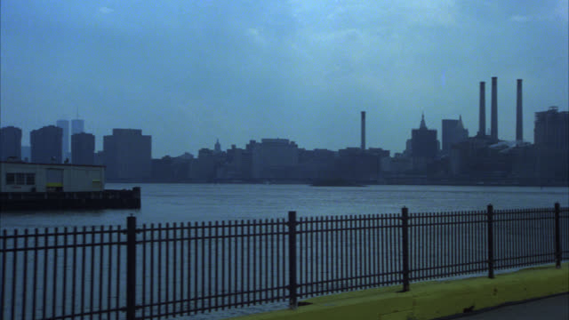pan left to right of new york city skyline. car parked in parking lot. east river. skyscrapers and high rise office buildings. manhattan. - 1980 stock videos and b-roll footage