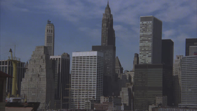 pan right to left up to skyscrapers and high rise office or apartment buildings in downtown manhattan. world trade center or twin towers in bg. brooklyn bridge. east river. american flag. - 1980 stock videos and b-roll footage