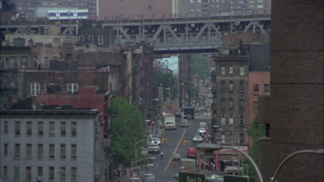 pull back from subway train on elevated tracks or bridge over cars on city street to high rise brick office building. one police plaza. police precinct, station or headquarters. freeway or highway in fg. downtown. urban area. - 1979 stock videos & royalty-free footage