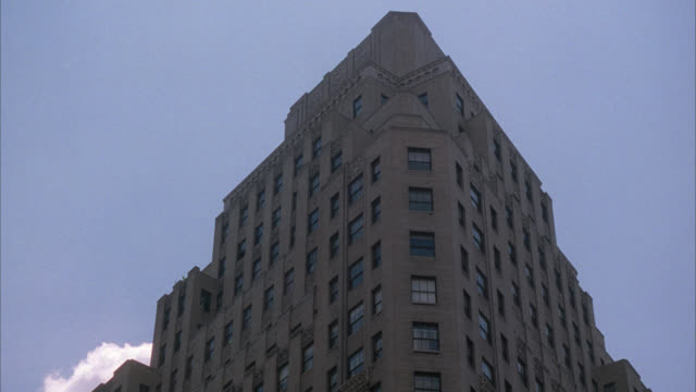 pan up of broadway building. high rise brown building with american flags hanging over entrance. camera pans up to see blue sky. manhattan, new york city. camera zooms in to upper story window. - broadway manhattan stock videos & royalty-free footage