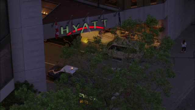 stockvideo's en b-roll-footage met up angle to hyatt regency high rise hotel. camera pans down to street level and traffic with silver gray avanti car driving on street. luxury car. - hyatt
