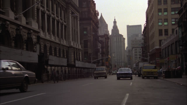 pan up from cars and police car driving on city street to 19th century building, former nypd headquarters. could be government office building. downtown. - 1979 stock videos & royalty-free footage