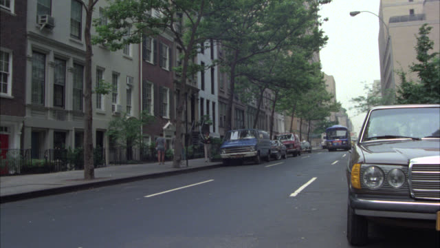 wide angle of middle class residential street in new york. cars parked on curb. city bus drives by from right to left and camera zooms in to second story window of apartment building with flower boxes. could be brownstone. pedestrians. - 1979 stock videos & royalty-free footage