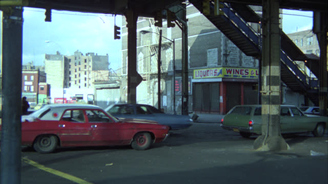 wide angle of nyc street under elevated train bridge or overpass. cars, pedestrians, and city bus. shops and storefronts in bg. lower class urban area. - 1977 stock videos & royalty-free footage