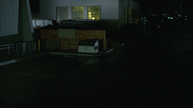 high angle down of convertible sports car, ford mustang, lights on, driving into warehouse. industrial area or building. - ford mustang stock videos and b-roll footage