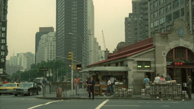 pan right to left from new york train station or subway entrance to cars driving on city street. man walks across crosswalk. grays papaya hot dog stand in bg. city bus visible. - 1984 stock videos & royalty-free footage