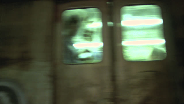 pan up from tracks in underground subway tunnel to train covered in graffiti. - 1984 stock videos & royalty-free footage