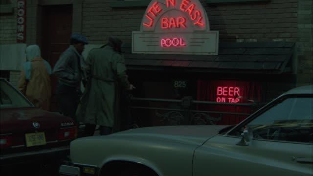 """vídeos y material grabado en eventos de stock de medium angle of neon sign for """"lite n easy bar and pool."""" under ground level bar. pedestrians on sidewalk. man enters and exits bar. - salón de billares"""