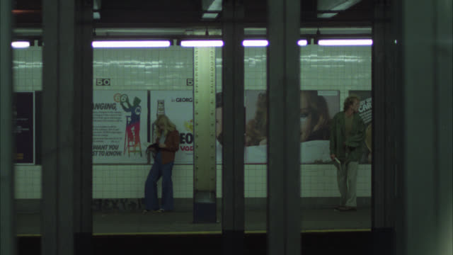 wide angle of underground subway station. cu of subway train going by. 50th street subway station. holdup of woman. she is shot as subway trains go by. gun. crime scenes. neg cut. - new york stock-videos und b-roll-filmmaterial