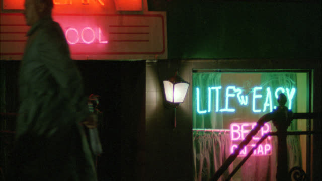 """medium angle of neon sign for """"lite n easy"""" bar. could be pool hall. man exits bar. woman hails taxi and follows man. urban area. rain. - anno 1987 video stock e b–roll"""