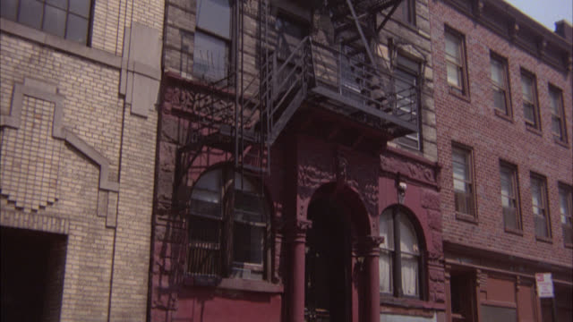 pan up from car driving on city street in urban area to fire escape on side of multi-story brick building, apartment building. - fire escape stock videos and b-roll footage