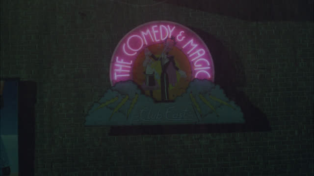 """medium angle of neon sign for """"comedy and magic club."""" could be bar or night club. pedestrians in raincoats with umbrellas. man in fg jumps into taxi. rain. - waterproof clothing stock videos and b-roll footage"""