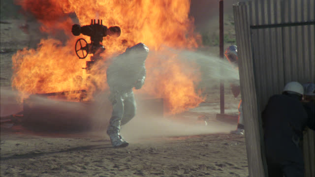 vídeos y material grabado en eventos de stock de wide angle of men in silver suits fighting fire at an oil pump in the desert. people standing behind metal wall spray water on fire. flames. stunt. action. - bomba de petróleo