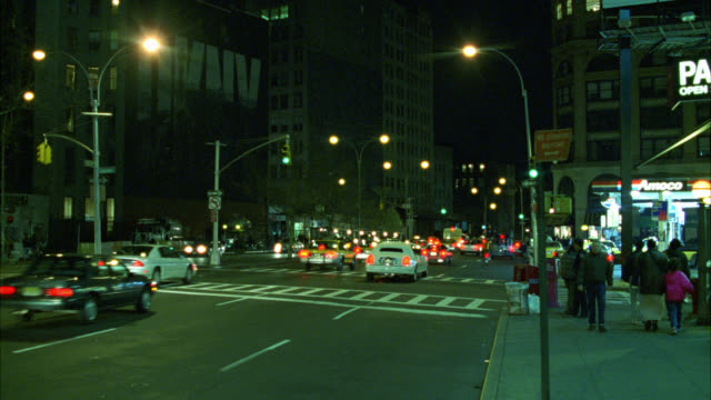 vídeos y material grabado en eventos de stock de wide angle of nyc street busy with traffic and yellow taxis. headlights. pedestrians.  silver avanti drives by left to right. luxury car. street lights. series. - 1999