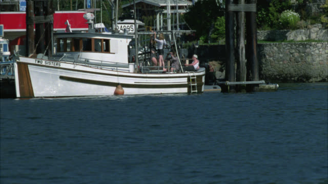 """stockvideo's en b-roll-footage met wide angle of fishing boat docked at harbor or marina. boat named """"two sisters."""" two women on deck of boat dance for two men sitting at stern. could be party. water visible. - men"""