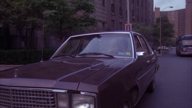 pan left to right from a car drives toward camera city street cm pans with actor leaving car walks to and up steps of  criminal courts building - 1980 stock videos and b-roll footage