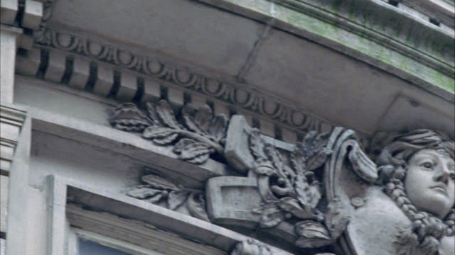 vídeos de stock e filmes b-roll de close angle of stone carvings on side of building. could be side of church. see bare tree branches in foreground. camera pans up to see window with balcony. - bare tree