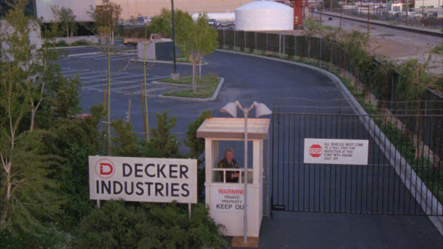 wide angle of large industrial manufacturing facility building plant surrounded by security gate with guard shack office  can work for privately private owned company sign reads  decker industries see cargo truck van pickup pull out of parking lot cam hol - 掘建て小屋点の映像素材/bロール