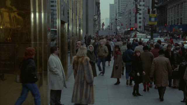 wide angle of pedestrians, people walking on sidewalk of new york city street past trump tower. man walks towards camera, enters trump towers building. high rise and skyscraper office buildings in bg. - manhattan bildbanksvideor och videomaterial från bakom kulisserna