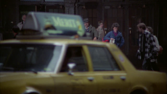 pull back from man exiting building, buying item from pretzel and hot dog vendor on street corner to show man walking across nyc street in front of grand central station with taxis, cars driving on street. pedestrians on sidewalk. train station. - anno 1984 video stock e b–roll