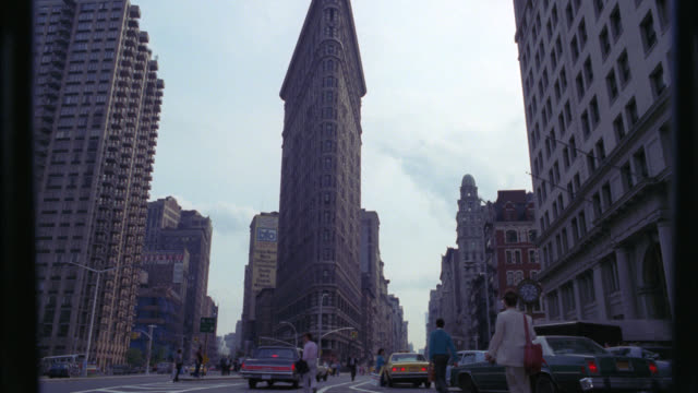 up angle of flatiron building or fuller building in new york city. fifth avenue. skyscrapers. pedestrians, people walking and cars, city buses and taxis driving on street. landmarks. cities. - 1986 stock videos and b-roll footage