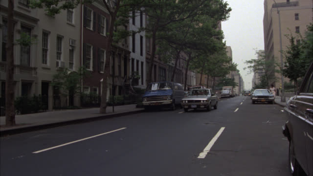 pan right to left across city street in residential area to middle class multi-story brownstone or brick apartment building or row house. zoom in on window. - middle class stock videos & royalty-free footage