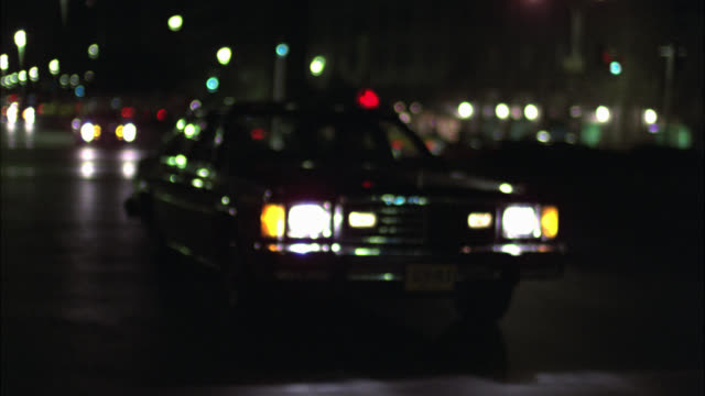 WIDE ANGLE DRIVING POV 3/4 RIGHT BACK AT CAR DRIVING FROM 54TH STREET TO 57TH STREET. HIGH RISE OFFICE OR APARTMENT BUILDINGS IN BG. FLASHING LIGHT, POLICE CAR. PARK AVENUE.