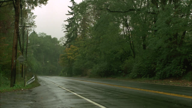 pan left to right of cars driving on street through country or rural area. trees of woods and forest. streets wet from rain. - 1991 stock videos and b-roll footage