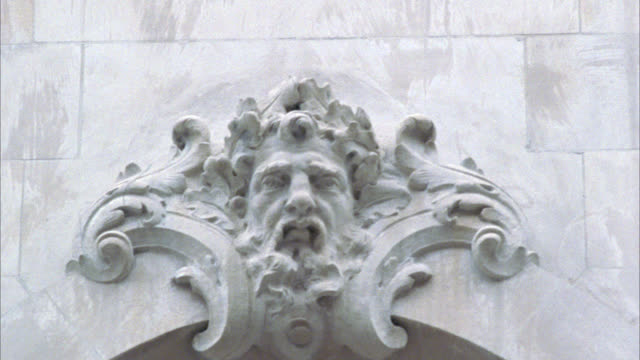 close angle of stone carvings on side of building. could be side of church. see bare tree branches in foreground. camera pans down to see window with balcony. interior lights are on. - carving craft product stock videos & royalty-free footage