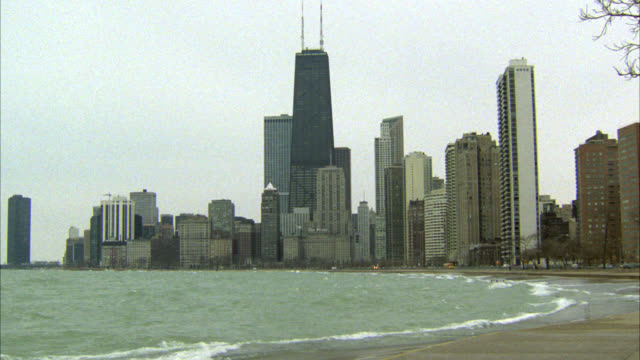wide angle of lake michigan and chicago city skyline from lakeshore drive. shore or beach of lake michigan. high rises and skyscrapers. overcast. sears tower. - 1982 stock videos and b-roll footage