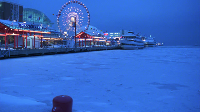vidéos et rushes de wide angle of navy pier or boardwalk. amusement park with lights on ferris wheel. cruise ships, boats docked in harbor. ice and snow on surface of lake michigan. - allée couverte de planches