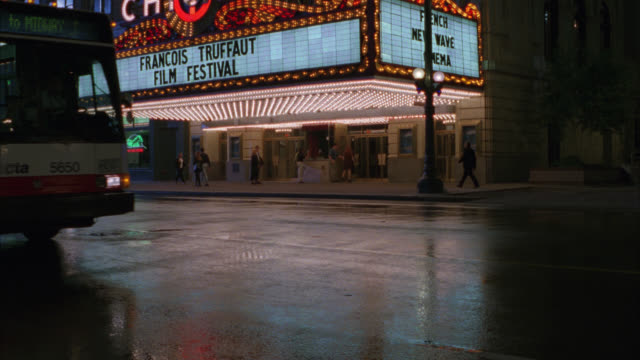 "vídeos y material grabado en eventos de stock de wide angle of ""chicago"" movie theatre house with neon sign and marquee. lights. sign reads ""francois truffaut film festival."" man walks into shot. - 1996"
