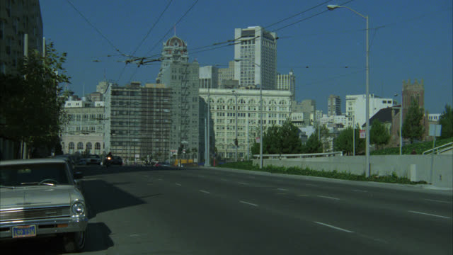 pan left to right of man riding on motorcycle down city street. high rise office buildings in bg. - 1985年点の映像素材/bロール