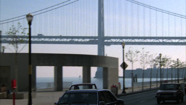 """PULL BACK FROM BAY BRIDGE TO CARS DRIVING ON CITY STREET PAST BRICK BUILDING WITH SIGNS NEXT TO DOOR THAT READ """"BUTLER SHIPPING"""" SECURITY GUARD STANDING NEXT TO DOOR. PEDESTRIANS, PEOPLE WALKING PAST BUILDING."""