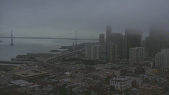 vidéos et rushes de pan left to right from bay bridge over san francisco bay to high rise and skyscraper office buildings, transamerica pyramid,  in san francisco financial district. cityscapes. fog. cities. san francisco skyline.3278 for nx - transamerica pyramid san francisco