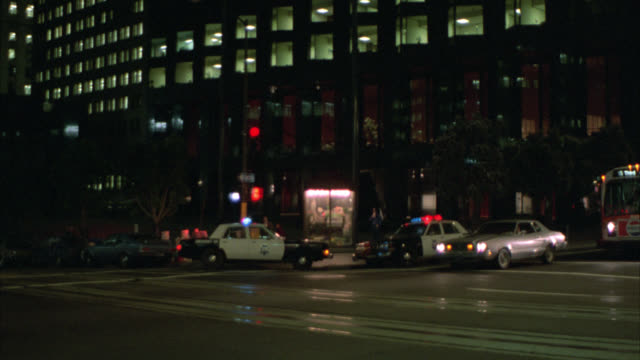 pan up high rise glass office building. police cars with flashing lights or bizbars parked on street below. could be city street. san francisco. - police car stock videos and b-roll footage