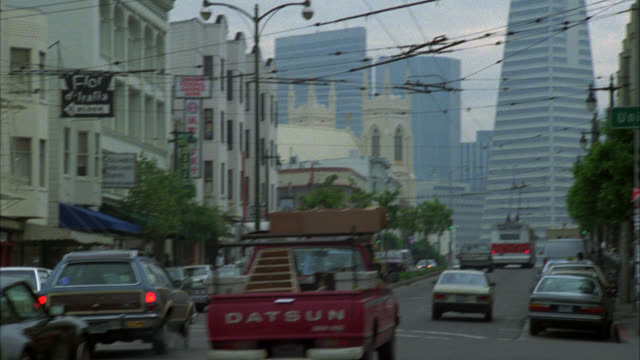 pan right to left of cars, cadillac driving on columbus street through commercial area. transamerica pyramid. city streets. - 1985年点の映像素材/bロール