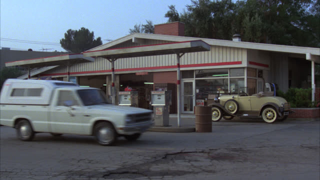 zoom in from cars driving by gas station to regular and unleaded gas pumps. classic car parked in front. - fuel pump stock videos and b-roll footage