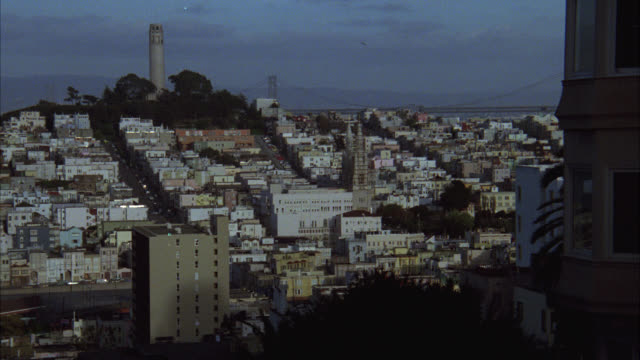 pan right to left of coit tower and telegraph hill and bay bridge in bg, cityscape, buildings, houses. street light in fg. san francisco bay. - coit tower stock videos & royalty-free footage