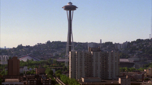 wide angle of space needle and high rise grosvenor hotel. seattle skyline or cityscape. monorail train on track below. landmarks. - 1986 stock-videos und b-roll-filmmaterial