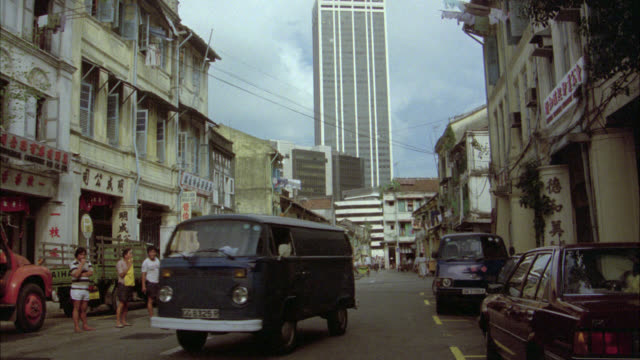 zoom in from cars driving, pedestrians , people walking and man riding a bike on city street in lower class area to high rise office building, glass building in bg. foreign city. asia. shops on both sides of street. - 1985 stock videos & royalty-free footage