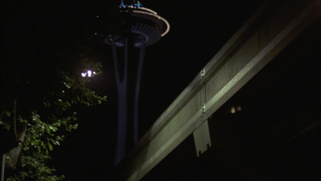 vídeos de stock e filmes b-roll de up angle to space needle in seattle. monorail train on elevated track. observation deck and restaurant. landmarks. - space needle