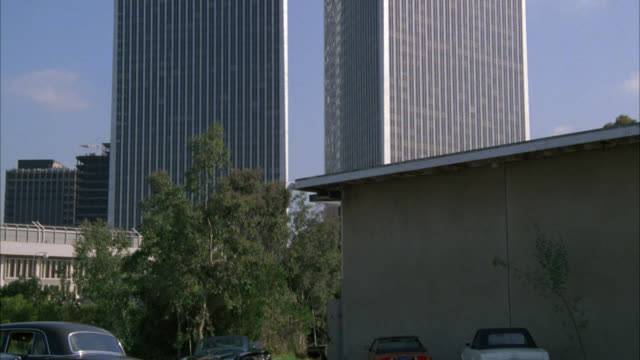pan down from century plaza towers, high rise office buildings to men driving in rolls royce car. - century city stock-videos und b-roll-filmmaterial