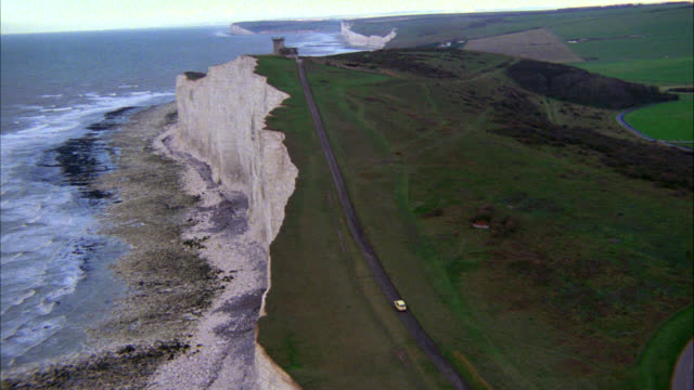 aerial of compact car driving on country road along cliffs and coastline. waves crashing on rocky beach, and grassy plains beyond road. car stops at isolated lighthouse. could be sussex, england, cliffs of dover. english channel. - dover england stock videos and b-roll footage