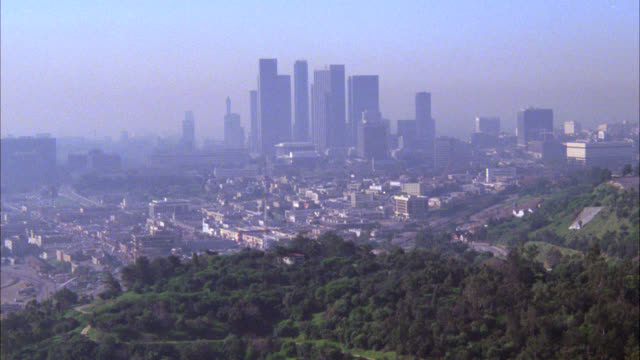 "aerial air-to-air tracking shot of ""bt""  black helicopter over city. high rise and skyscraper office buildings in downtown los angeles in bg. - anno 1983 video stock e b–roll"