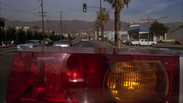 WIDE ANGLE DRIVING POV STRAIGHT FORWARD FROM BEHIND BIZBAR OR FLASHING LIGHTS OF OLIVE AVENUE. COULD BE POLICE CAR, FIRE TRUCK OR AMBULANCE. RED AND YELLOW LIGHTS. MOUNTAINS IN BG. SAN FERNANDO VALLEY. COULD BE EMERGENCY. SIGNS FOR GENIO'S RESTAURANT AND