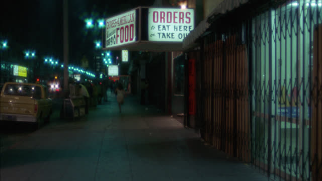 wide angle of principal actor, woman, running down sidewalk of city street in urban area. sign for take-out food. restaurant. could be downtown. - 1975 stock videos and b-roll footage